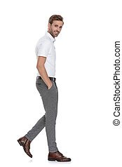 side view of a relaxed young smart casual man walking