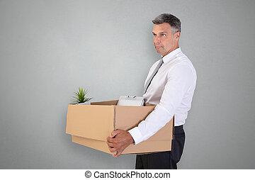 Sad Businessman Carrying Belongings In Cardboard Box