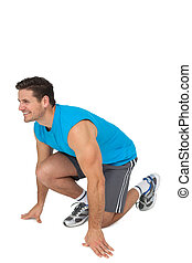 Side view of a sporty smiling man in running stance - Side...