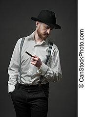 Side view of a stylish young man with suspenders smoking cigar