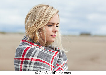 Side view of a woman covered with blanket at beach - Close...