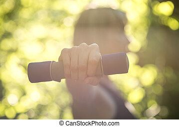 Side view of a woman exercising wth dumbbells in nature