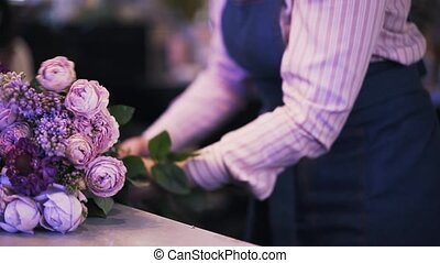 Side view of a woman florist making a purple bouquet, pan shot