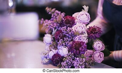 Side view of a woman florist making a purple bouquet
