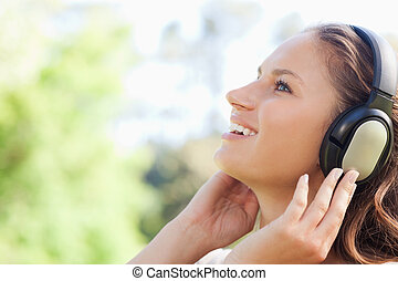 Side view of a woman in the park listening to music