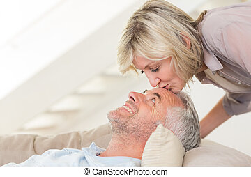 Side view of a woman kissing a relaxed mature mans forehead...