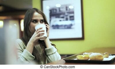 Side view of a woman on the phone in a cafe
