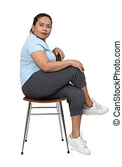 side view of a  woman sitting on a chair looking at camera on white background, arms crossed