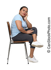 side view of a  woman sitting on a chair looking at camera on white background