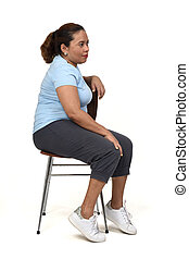 side view of a  woman sitting on a chair looking at the side on white background