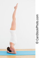 Side view of a woman standing upside down on exercise mat