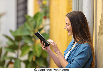 Side view of a woman using a tablet in the street