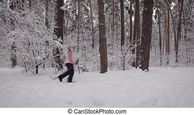 Side view of a woman who is energetically in the winter park. Around her, pines and other spruce trees.