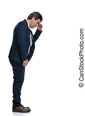 Side view of a wondering businessman looking down for something