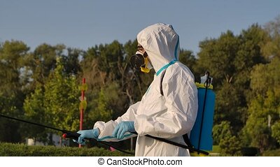 Side view of a worker disinfecting outdoors in a public park with a spray of antibacterial disinfectant. Man in respiratory gas mask and a protective suit with a pressure washer close up. Slow motion.