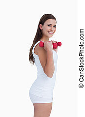 Side view of a young brunette holding dumbbells