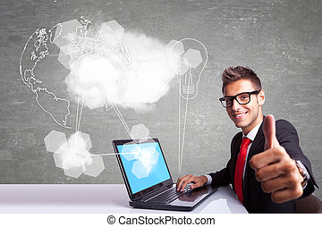 side view of a young business man working at his laptop computer and making the ok thumbs up sign while connecting to internet and the world