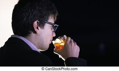 Side view of a young businessman drinking whiskey in his office at night