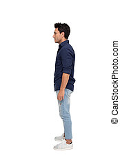 Side view of a young casual man standing isolated on white background