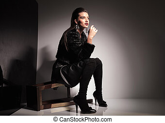 young casual woman sitting on a stool