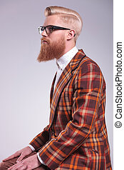 side view of a young fashion man with long beard and glasses looking away