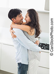 Side view of a young man embracing woman in kitchen