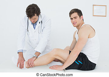 Side view of a young man getting his ankle examined at the...