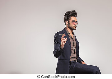 young man in suit holding a cigarette