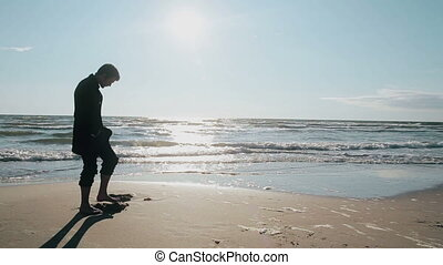 Side view of a young man standing barefoot on the beach on a lovely sunny day digging a hole in the sand with his toes.