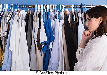 Woman Looking At Clothes On Clothes Rail