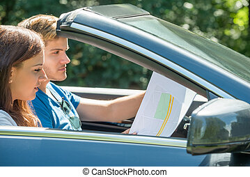 Woman Looking At Map While Man Driving Car