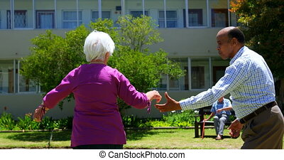 Side view of active mixed-race senior couple dancing together in the garden of nursing home 4k