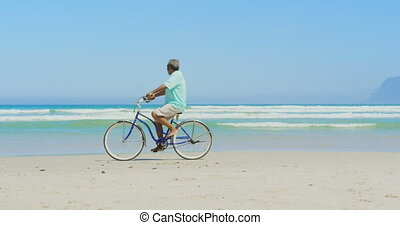Side view of active senior African American man riding bicycle on beach in the sunshine 4k