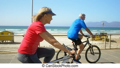 Side view of active senior Caucasian couple riding bicycle on a promenade at the beach 4k
