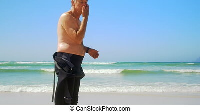 Side view of active senior Caucasian male surfer standing on...