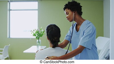 Side view of African american female doctor examining female patient in the ward at hospital