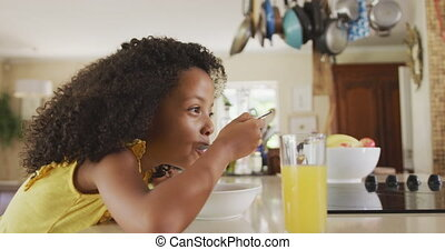 Side view of African american girl eating cereals - Side ...