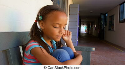 Side view of African American schoolgirl sitting on bench and crying in school corridor 4k
