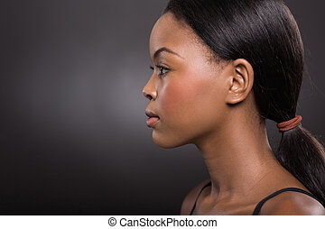 side view of african american woman on black background