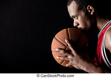 side view of african sporty man holding basketball ball on black
