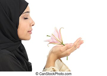 Side view of an arab woman wearing a hijab smelling a flower