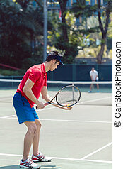 Asian tennis player ready to serve at the beginning of a doubles mixed match