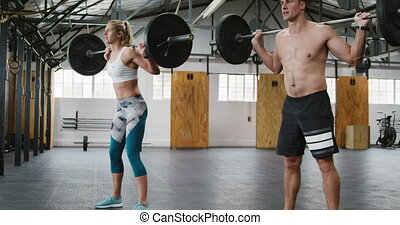 Side view of an athletic Caucasian man and woman wearing sports clothes cross training at a gym, standing and weight training with barbells, squatting down and rising holding the barbells on their shoulders, the man is shirtless