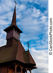 Side view of an old wooden church on a cloudy sky in Maramures