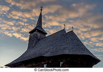 Side view of an old wooden church with bell tower on a cloudy blue sunset sky in Maramures