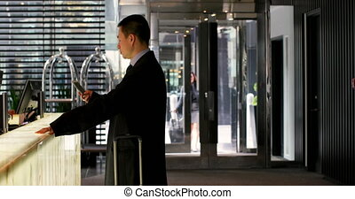 Side view of asian businessman using mobile phone at ...