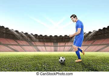 Side view of asian football player man kicking the ball