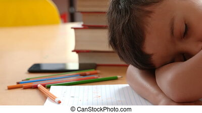 Side view of Asian schoolboy sleeping on desk in classroom at school 4k