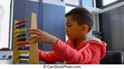 Side view of Asian schoolboy solving math problem with abacus at desk in a classroom at school 4k