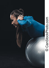 Side view of athletic young woman in sportswear exercising with fitness ball